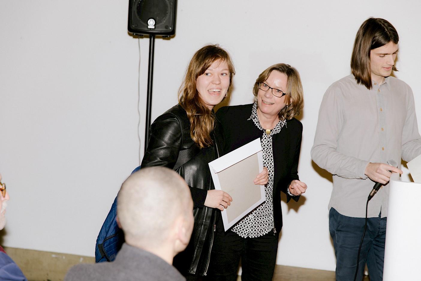 Line Lyhne nimmt den Preis bzw. das Reisestipendium für sich und Pia Ferm von Silke Bernbeck entgegen